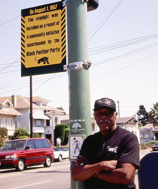 David Hilliard standing under the Black Panther Party marker