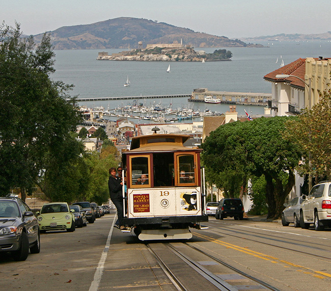 Powell & Market Cable Car climbing up Russian Hill with Fishermans Wharf and Alcatraz in background